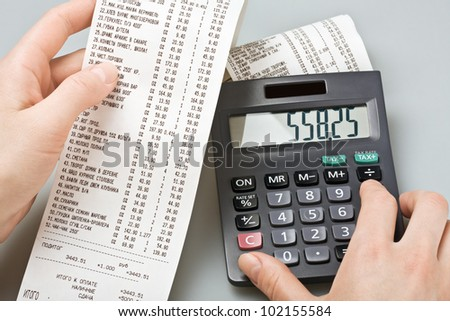 check and consider purchases on the calculator - stock photo