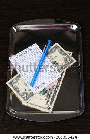 Check and money of coffee on tray close-up - stock photo