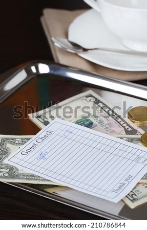 Check and money on tray close-up - stock photo