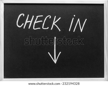 Check in message and arrow pointing downwards written with white chalk on blackboard - stock photo