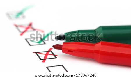 Check list with green and red pen over white paper - stock photo