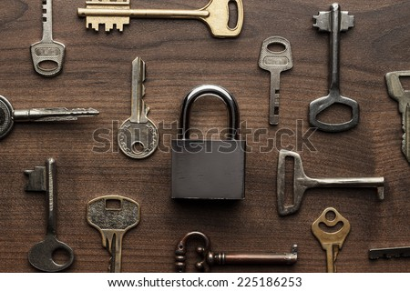 check-lock and different keys on wooden background concept