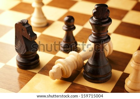 Check mate as a vanquished king lies on its side at the end of a game of chess surrounded by the opposing black chess pieces - stock photo