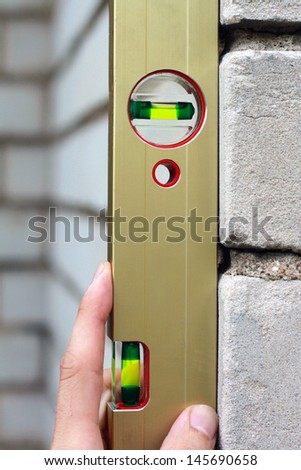 check the level of a brick house wall - stock photo