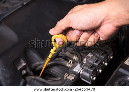 check the oil level in car engine - stock photo