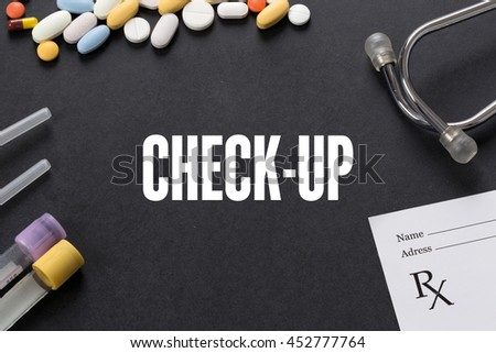 CHECK-UP written on black background with medication - stock photo