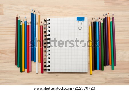 Checked blank notebook with blue binder clip and multicolored pencils on wood background. - stock photo