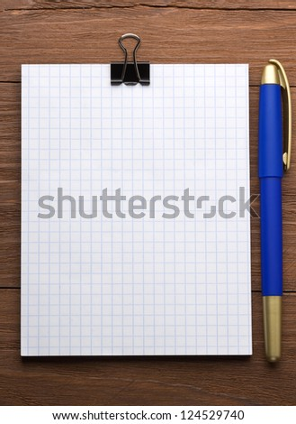 checked notepad and pen on wood background - stock photo