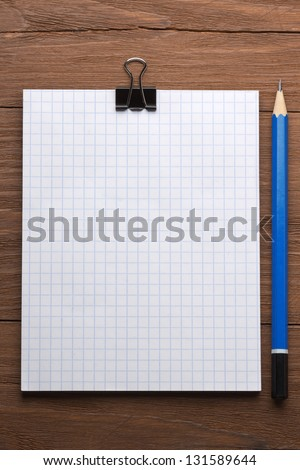 checked notepad and pencil on wood background - stock photo