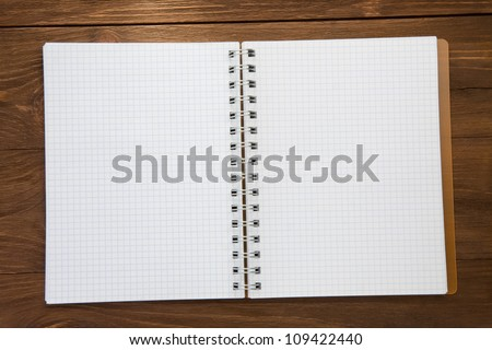 checked notepad  on wood background - stock photo