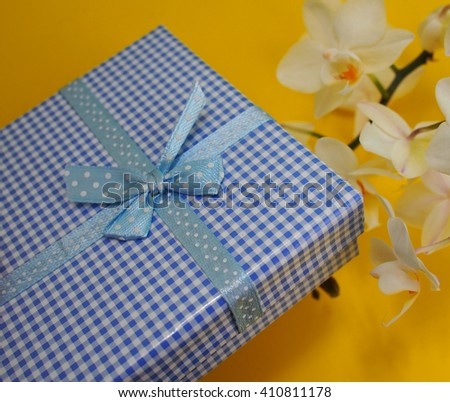 Checkered blue and white gift box with white orchid yellow background