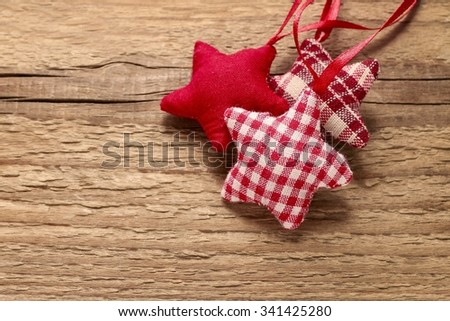 Checkered fabric christmas stars on wooden background, copy space - stock photo