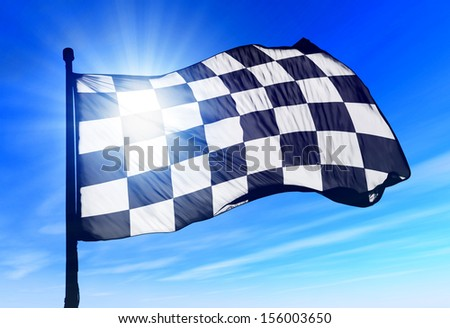 Checkered flag waving on the wind - stock photo