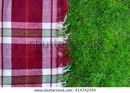 Checkered Plaid Picnic Green Grass Summer Time Background - stock photo