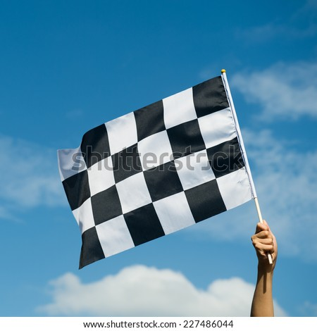 checkered race flag in hand. - stock photo