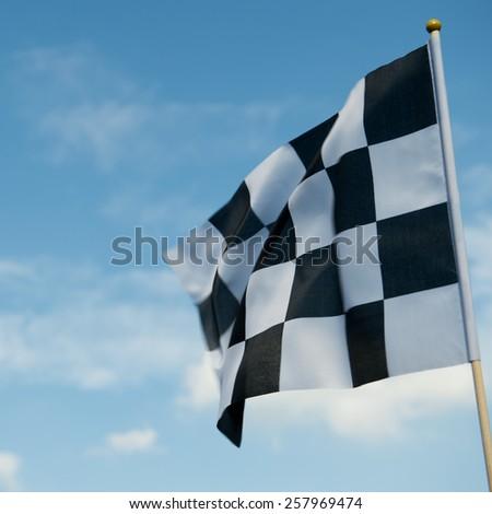 checkered race flag waving on blue sky. - stock photo