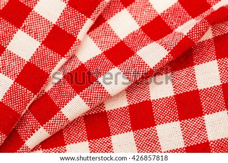 Checkered red white folded with pleats tablecloth background - stock photo