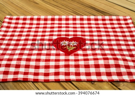 Checkered red white tablecloth  on wooden table rustic background - stock photo