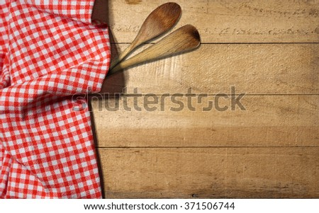 Checkered Tablecloth on Wooden Table / Rustic wooden table partially covered with a red and white checkered tablecloth and two wooden spoons or ladles  - stock photo