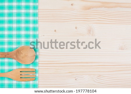 Checkered tablecloth, spoon, fork on wooden table background - stock photo