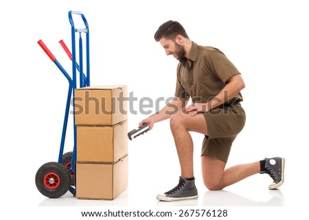 Checking a delivery. Smiling courier kneeling close to carton box and holding digital equipment. Full length studio shot isolated on white. - stock photo