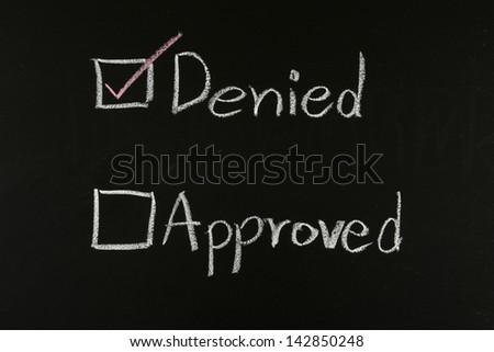 checking denied written on blackboard - stock photo