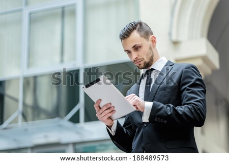 Checking e-mail. Young man in formal wear holding a tablet in his hands lookung in screen. Businessman in formal wear seriously reading message