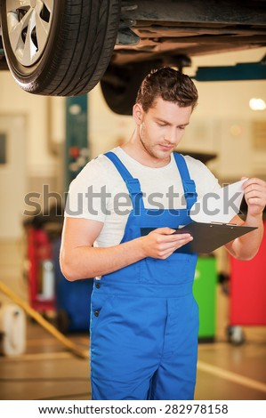 Checking every detail. Confident young man in uniform holding clipboard while standing in workshop