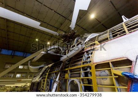 Checking helicopter systems and propellers in hangar - stock photo