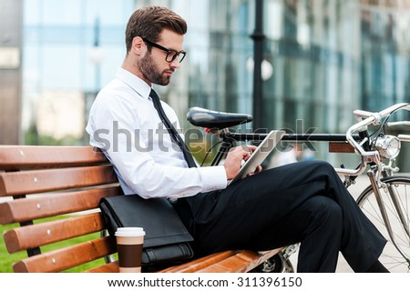Checking his business schedule. Side view of confident young businessman working on digital tablet while sitting on the bench near his bicycle with office building in the background - stock photo