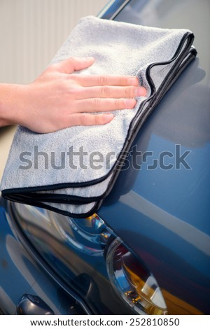 Checking his ideal work. Closeup of car mechanic hand polishing the luxury car with wiper in car repair shop - stock photo