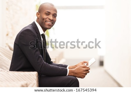 Checking his schedule on the go. Side view of cheerful young African businessman working on digital tablet and smiling at camera - stock photo