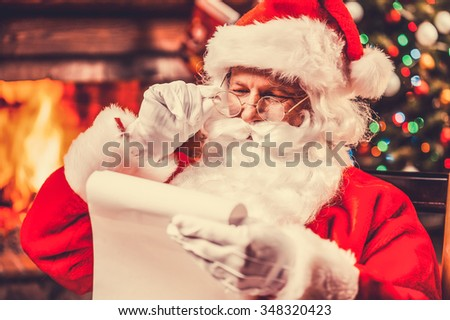 Checking his special list. Traditional Santa Claus sitting at his chair and reading a letter with fireplace and Christmas Tree in the background