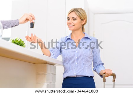 Checking in. Smiling young lady reaching out to take her personal room key.  - stock photo