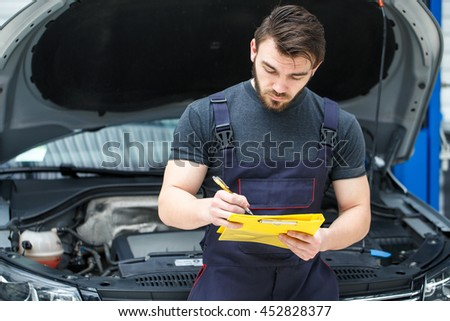 Checking info. Portrait of a bearded mechanic writing on his clipboard car on repair on the background