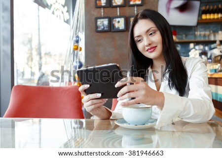 Checking latest news. Beautiful cheerful businesswoman using her tablet over a cup of coffee at the coffee shop
