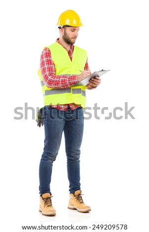 Checking list. Focused construction worker in yellow helmet and lime waistcoat holding a clipboard and writing. Full length studio shot isolated on white. - stock photo
