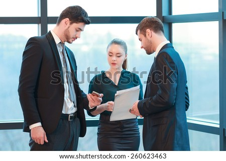 Checking schedule with colleagues. Group of business people in formal wear looking at the screen of mobile phone while standing against the window in the meeting room
