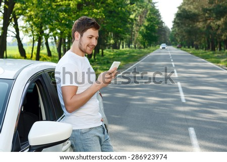 Checking social media. Young attractive smiling man with beard standing near his car and holding mobile phone