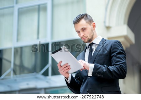 Checking statistics. Successful and confident businessman stands and checks online news on the tablet inside business center. Young business in formal clothes - stock photo