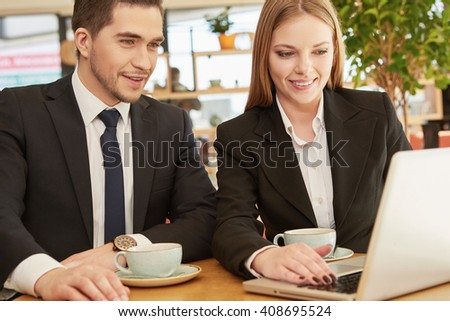 Checking stocks. Two business partners working on the laptop smiling cheerfully on a meeting at the local cafe - stock photo