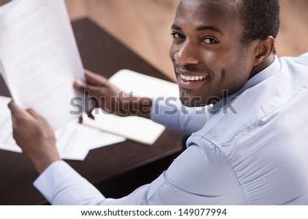 Checking the documents. Top view of cheerful African descent men writing something on the papers - stock photo