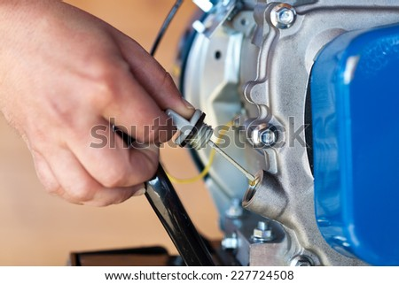 Checking the oil level in a small combustion engine - closeup on hand - stock photo