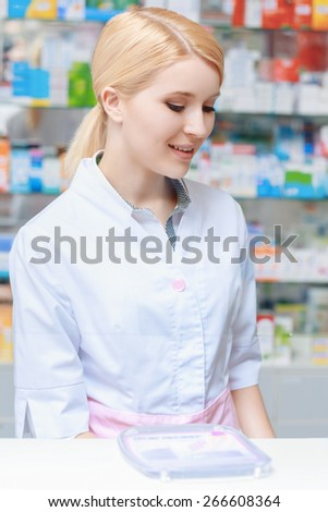 Checking the pharmacy stock. Young blond female pharmacist looking below while using computer at pharmacy counter - stock photo