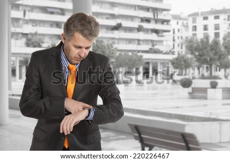 Checking the time. Worried adult businessman