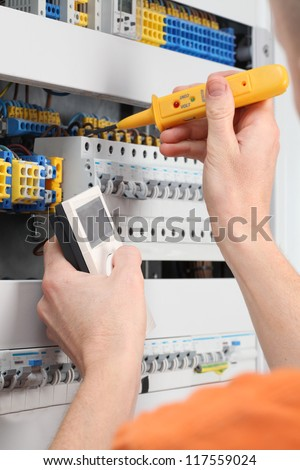 Checking voltage in switchboard with a detector - stock photo