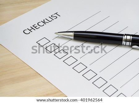 Checklist concept - checklist, paper and a pen with checklist word on wooden table - stock photo
