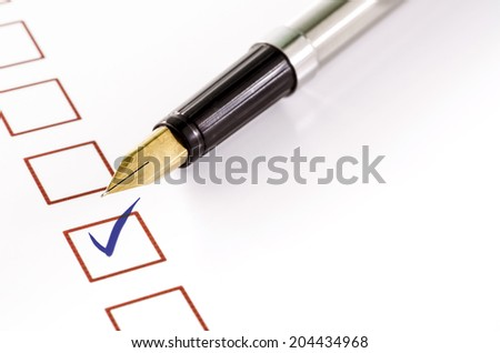 checklist with a ticked box and a pen on white paper