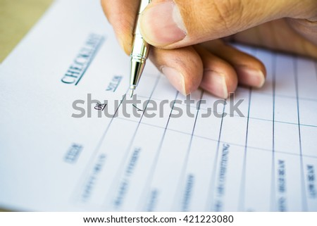 Checklist with metal pen. Selective focus image