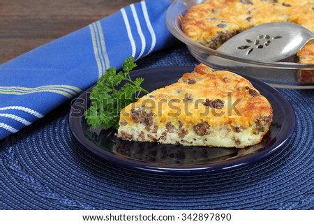 Cheddar cheese and beef pie, one portion with cut pie in background. - stock photo